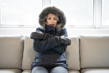 La donna ha il raffreddore sul divano di casa con il cappotto invernale