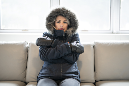 Woman have cold on the sofa at home with winter coat Imagens