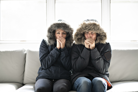 Couple have cold on the sofa at home with winter coat Фото со стока