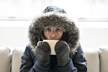 Mujer tiene café de bebida fría en el sofá en casa con abrigo de invierno Foto de archivo