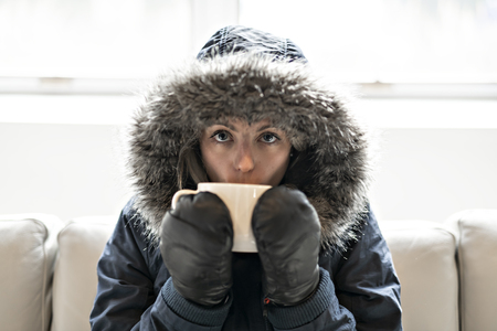 Woman have cold drink coffee on the sofa at home with winter coat Фото со стока - 112330875