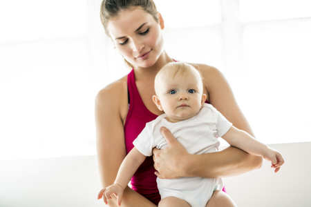 A Portrait of beautiful young mother in sports wear with her charming little baby in training session Stok Fotoğraf