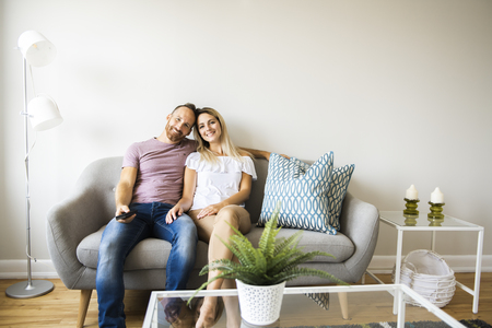 Couple watching tv at home sitting in a comfortable couch in the livingroom at home