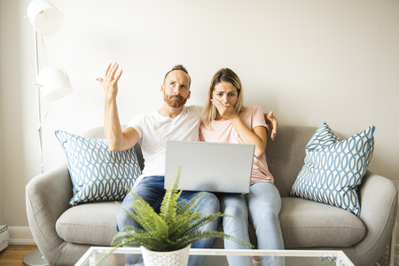 Portrait of a young man with his girlfriend on laptop at home indoor