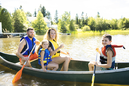 Family in a Canoe on a Lake having fun Фото со стока