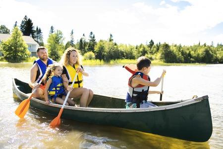 Familie in einem Kanu auf einem See, der Spaß hat