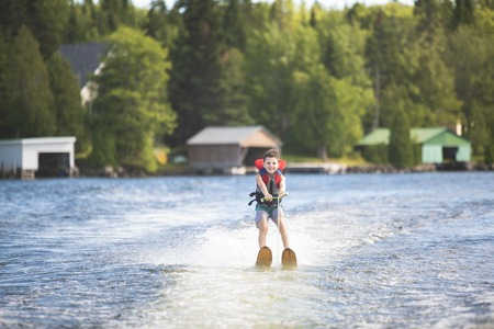 Child learning to water skiing on a lake Imagens