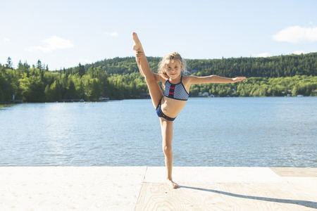 cute little girl doing some stretching close to a lake Standard-Bild