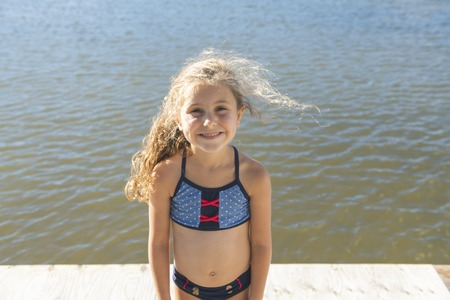 cute little girl stands smiling close to a lake Banque d'images