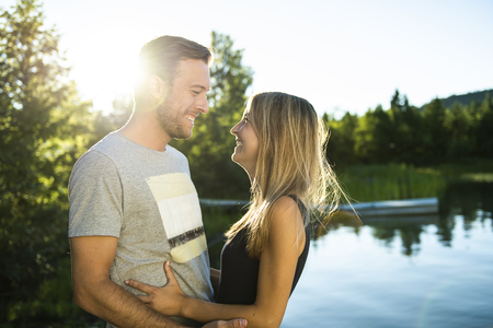 Couple outdoors by lake having good time