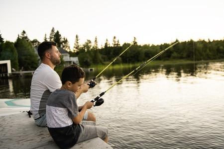 Cool Dad and son fishing on lake 免版税图像