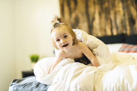 Cute little baby girl on bed at home