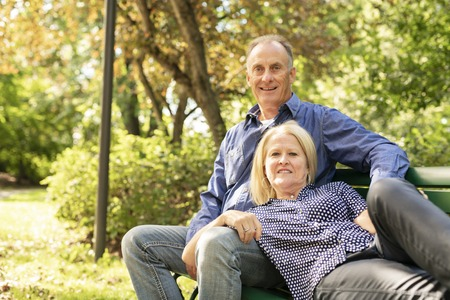 A Senior couple sitting on a park bench shallow depth of field