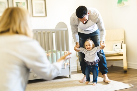 little baby girl first steps with the help of parent Standard-Bild