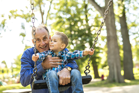 A Grandfather pushing his grandson on the rope swing