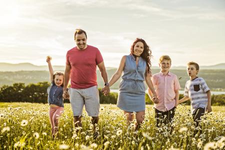 Glückliche Familie, die bei Sonnenuntergang Spaß auf dem Gänseblümchenfeld hat