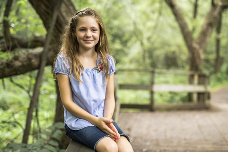 Portrait of a happy young girl outdoors forest