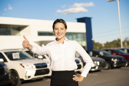 Young woman car rental in front of garage with cars on the background 免版税图像