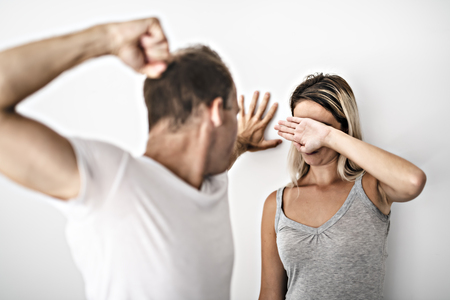 man beating helpless woman at home white background