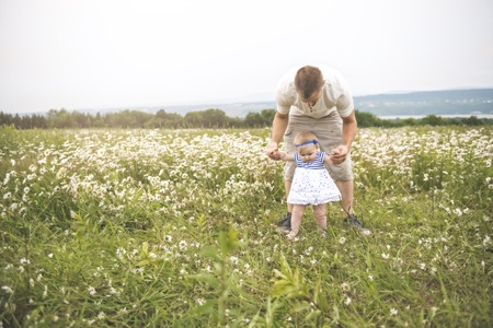 little baby girl and his father enjoying outdoors in field of daisy flowers Standard-Bild