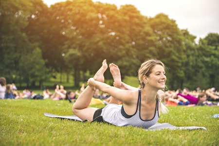 big group of adults attending a yoga class outside in park Imagens