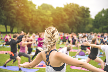 big group of adults attending a yoga class outside in park Stockfoto