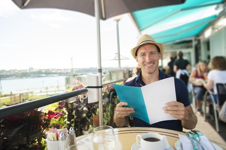 Young man sitting tourist sit for the breakfest with coffee holding menu