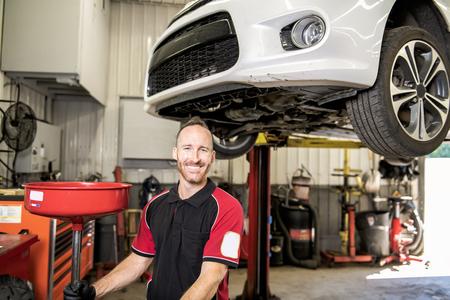 przystojny mechanik oparty na samochodzie w warsztacie samochodowym Zdjęcie Seryjne