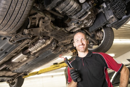 A Portrait of handsome mechanic based on car in auto repair shop Stock Photo