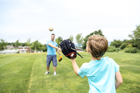 Handsome dad with his little cute sun are playing baseball on green grassy lawn Archivio Fotografico