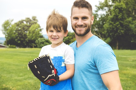 Handsome dad with his little cute sun are playing baseball on green grassy lawn Stock Photo