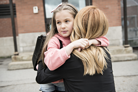A girl child and his mother hugging outside at school Фото со стока