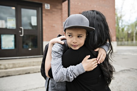 A boy child and his mother hugging outside at school
