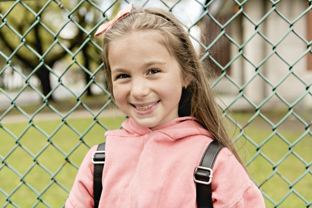 Portrait of cute girl with backpack outside of school 免版税图像
