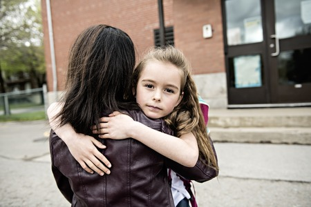 A girl child and his mother hugging outside at school Stock Photo