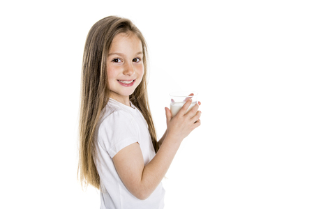 Portrait of a cute 7 years old girl Isolated over white background with milk glass