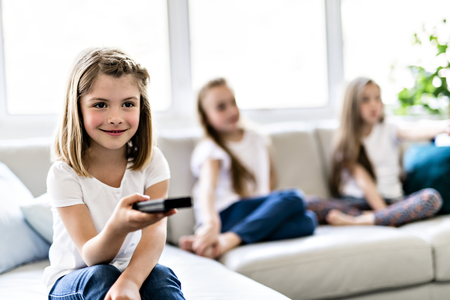 Three attractive child girls in casual clothes watching TV at home