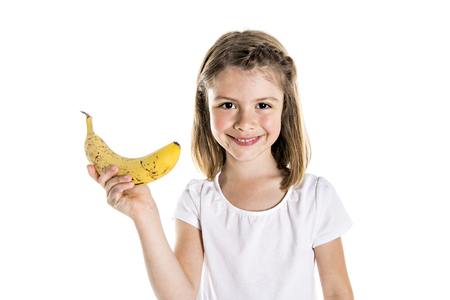 Portrait of a cute 7 years old girl Isolated over white background with banana Фото со стока