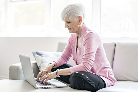 Retired senior woman sitting at home using her laptop