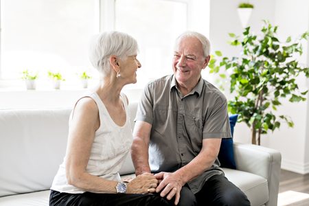 Affectionate attractive elderly couple sitting together on a couch