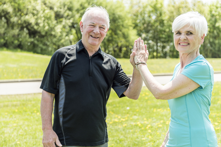 Senior couple running in park doing high five Standard-Bild