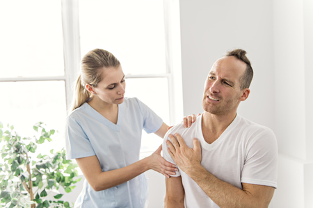 men Explaining Shoulder injury to the doctor
