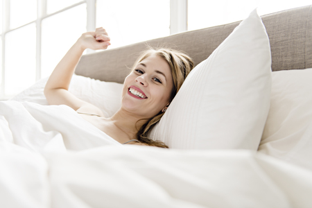 Beautiful young woman on bed, 20s year old Reklamní fotografie