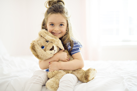 Sweet little girl is hugging a teddy bear on her bed at home