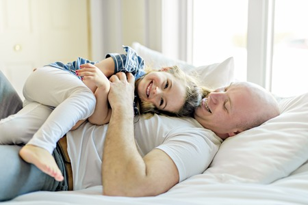 Happy father and daughter having fun together on a bed Banco de Imagens