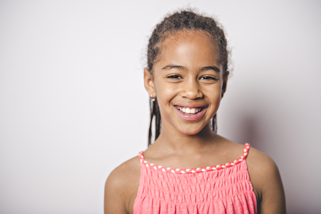 Cute nine years old child with pink dress on studio white background