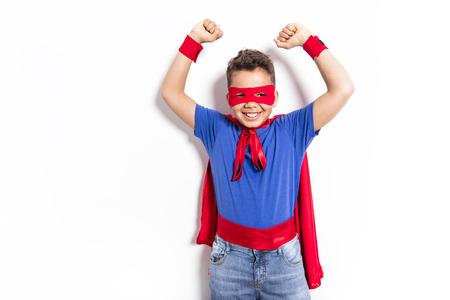Portrait of boy in superhero costume against grey background