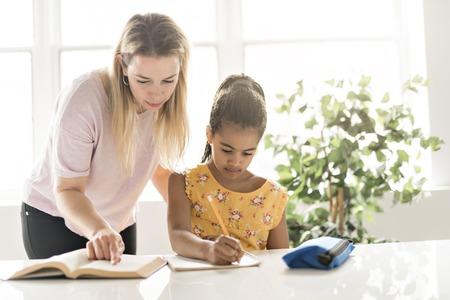 mother help Black girl doing homework at home Stock fotó
