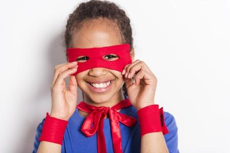 Portrait of girl in superhero costume against grey background
