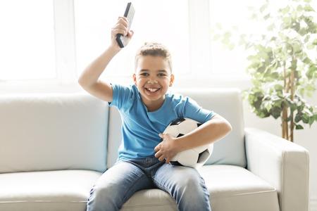 boy with soccer ball listening foot game on tv 版權商用圖片
